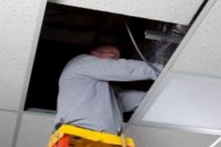 Man on ladder assembling ceiling lighting