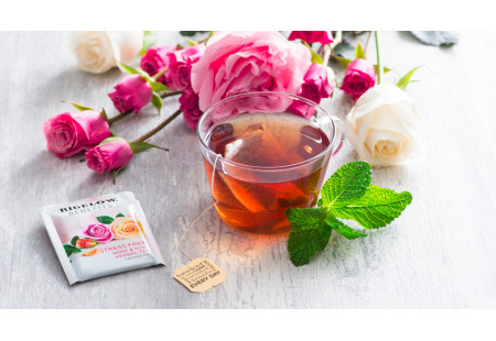 Lifestyle image of a cup of Rose and Mint herbal tea  with tea bag and foil wrap
