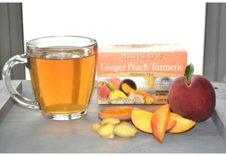 Glass mug of Ginger Peach Turmeric Tea and peaches