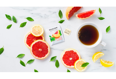Lifestyle image of a cup of Lean and Fit Citrus and Oolong tea with tea bag and foil wrap