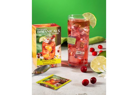 Glass of Cranberry Lime Honeysuckle Cold Water Infusion with tea box and foil