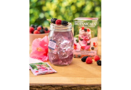Glass of  Blackberry Raspberry Hibiscus Cold Water Infusion with tea box and foil