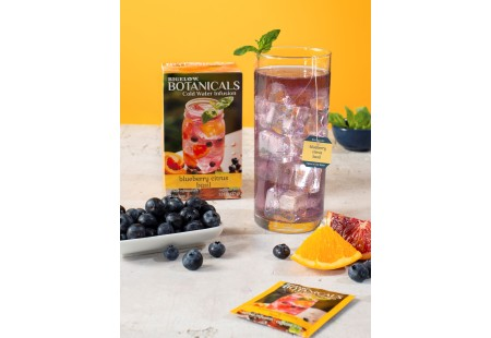 Glass of  Blueberry Citrus Basil Cold Water Infusion with tea box and foil
