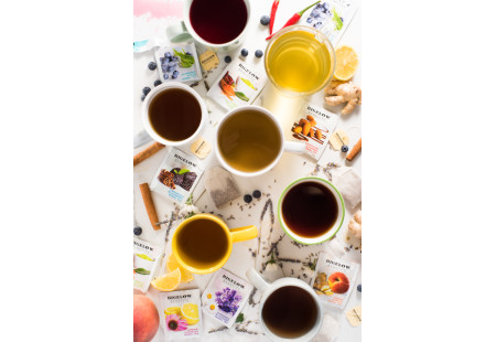 Cups of Bigelow Benefits Herbal and Green Tea boxes with ingredients