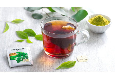 Lifestyle image of a cup of Moringa Black Tea with tea bag and foil wrap