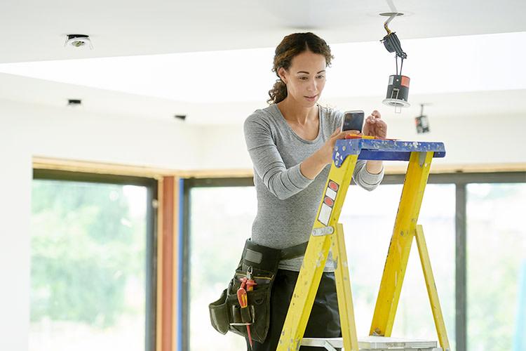 Woman on ladder adjusting light fixture