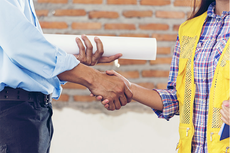 Man holding building plans shaking hands with female contractor