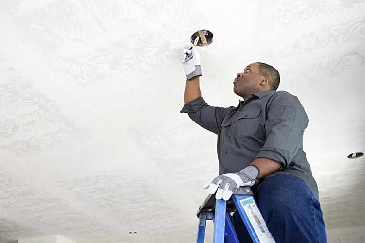 Man on ladder cutting round ceiling hole