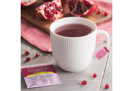Lifestyle image of a cup of Bigelow Pomegranate Pizzazz Herbal Tea