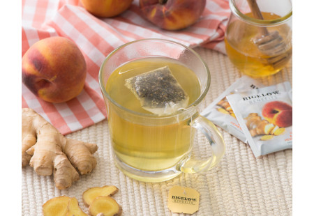 Lifestyle image of a cup of  Bigelow Benefits Ginger and Peach Herbal Tea