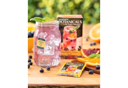 Mason jar filled with Blueberry Citrus Basil Cold Water Infusion with tea box and foil